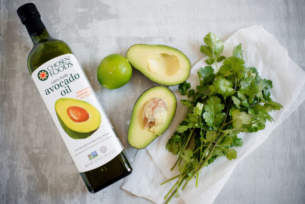 bottle of avocado oil, lime, avocado, and cilantro