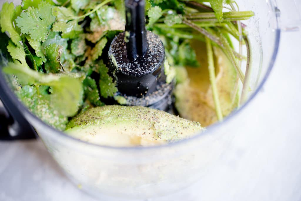 avocado, cilantro, and seasonings in a clear food processor