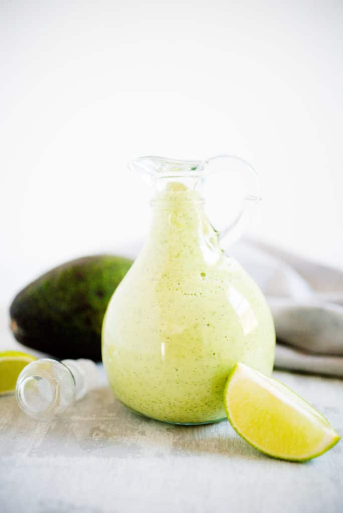 clear glass jar filled with avocado cilantro dressing with a bright green lime leaning against the bottle and an avocado in the background