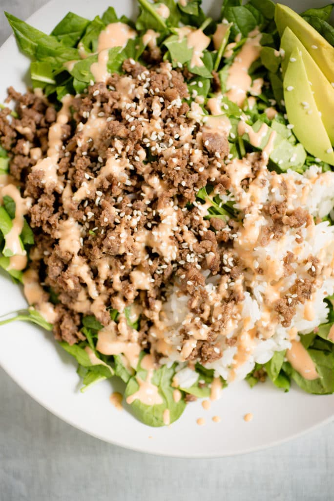 a bed of greens with avocado, korean beef, rice, spicy mayo, and white sesame seeds
