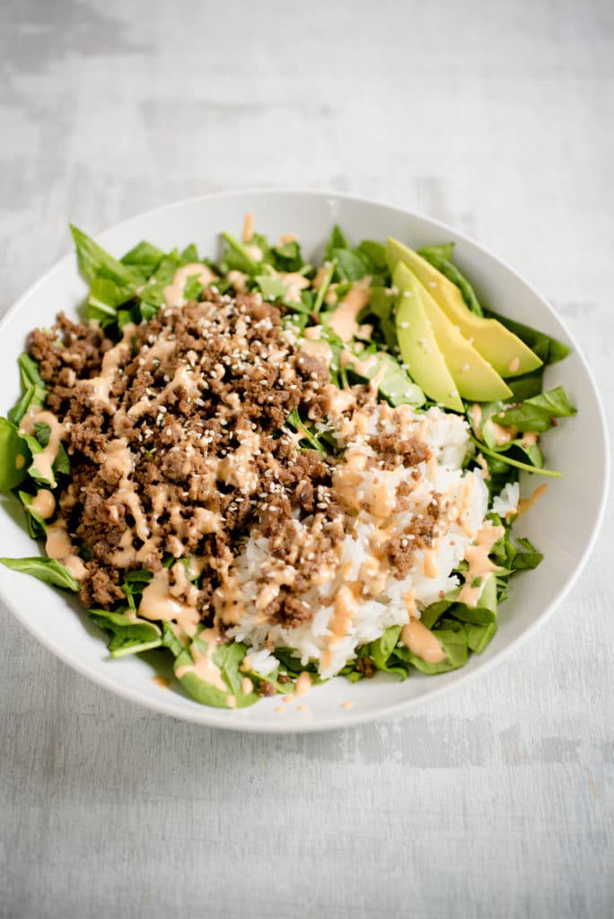 korean beef in a white bowl on top of lettuce greens with sliced avocado and rice. it is topped with spicy mayo and white sesame seeds