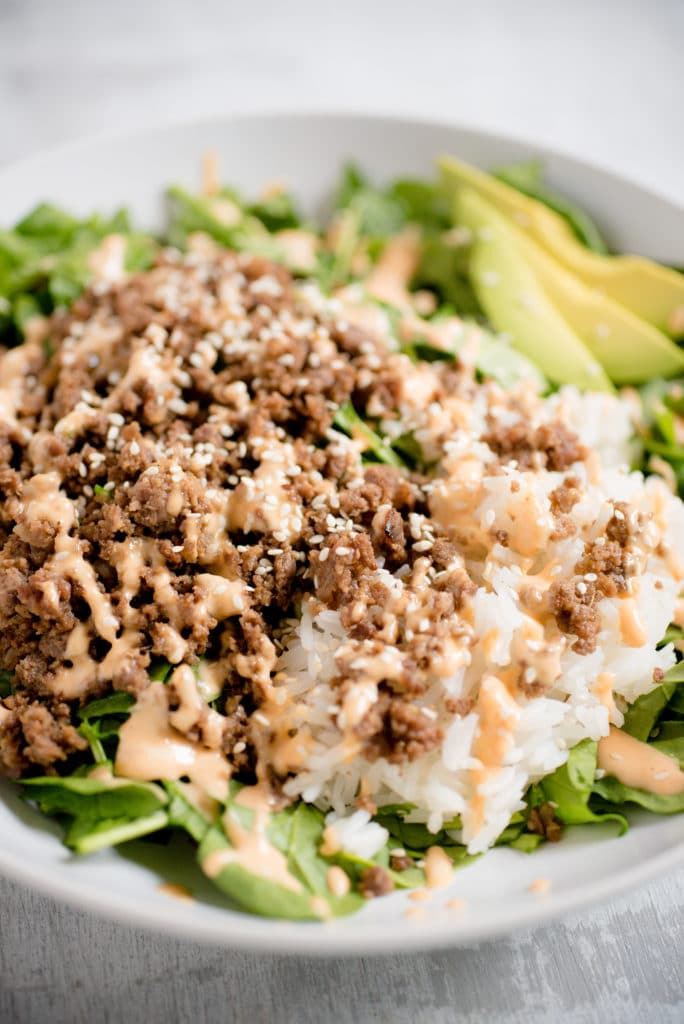 detailed view of greens topped with korean beef, rice, white sesame seeds, and spicy mayo with slices of avocado seen in the background