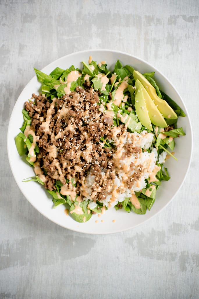 large white bowl with greens, korean beef, white rice, sliced avocado, white sesame seeds, and spicy mayo