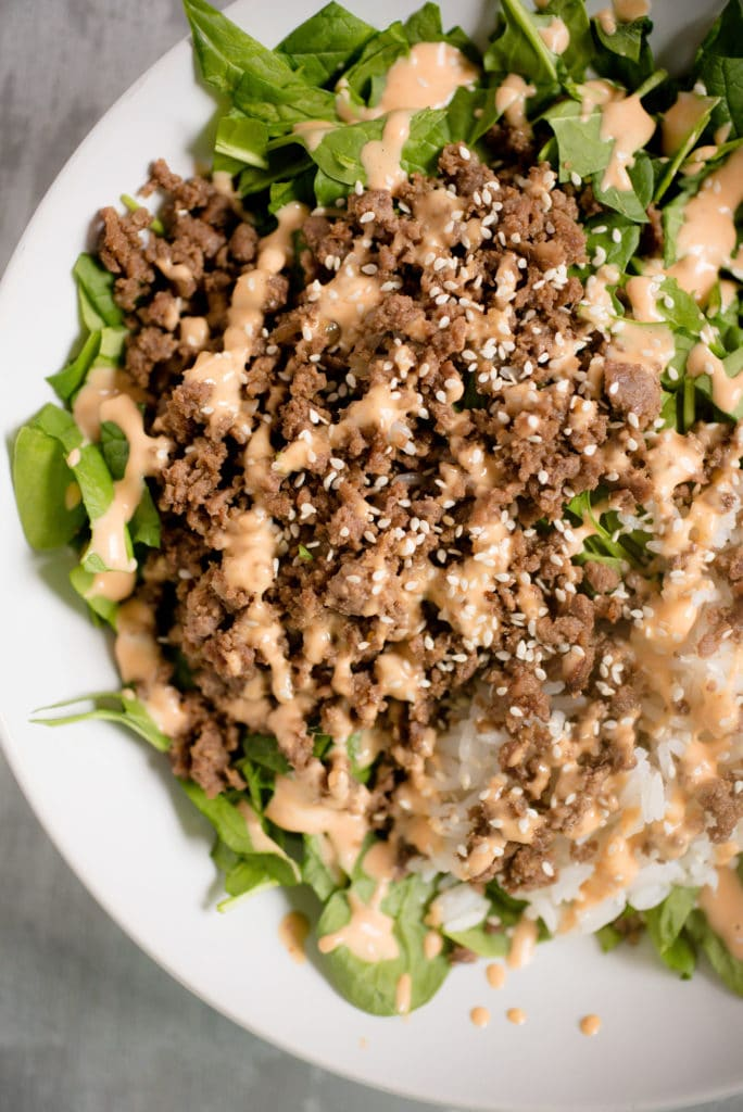 lettuce greens in a white bowl, topped with korean ground beef, white rice, spicy mayo and white sesame seeds