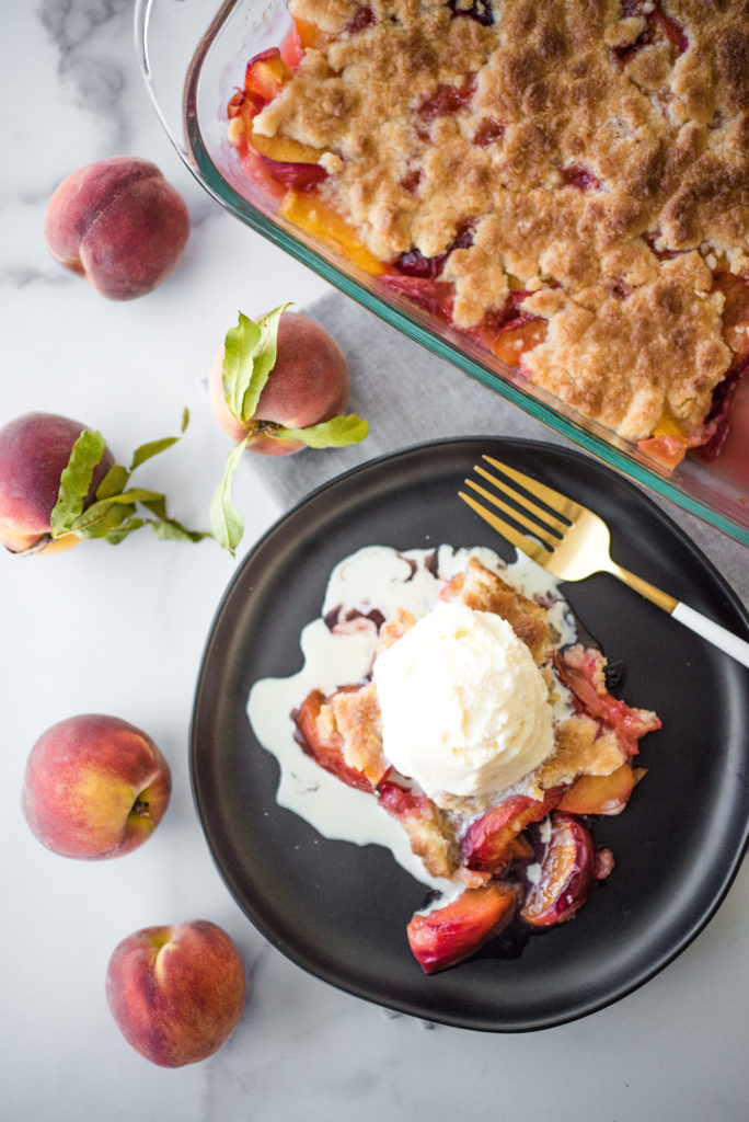 overhead shot of a slice of peach cobbler on a round, black plate topped with a scoop of vanilla ice cream. there is a gold and white fork resting on the plate and the remainder in a glass casserole dish surrounded by fresh peaches.