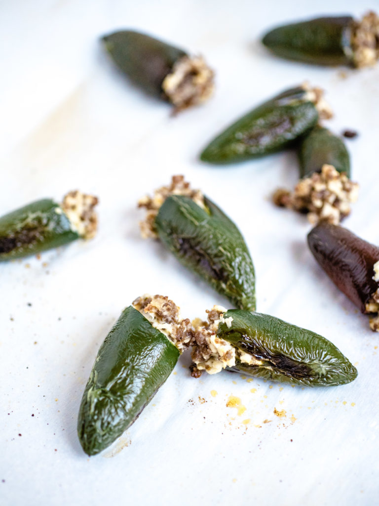 picture of several oven roasted stuffed jalapenos laying on parchment paper