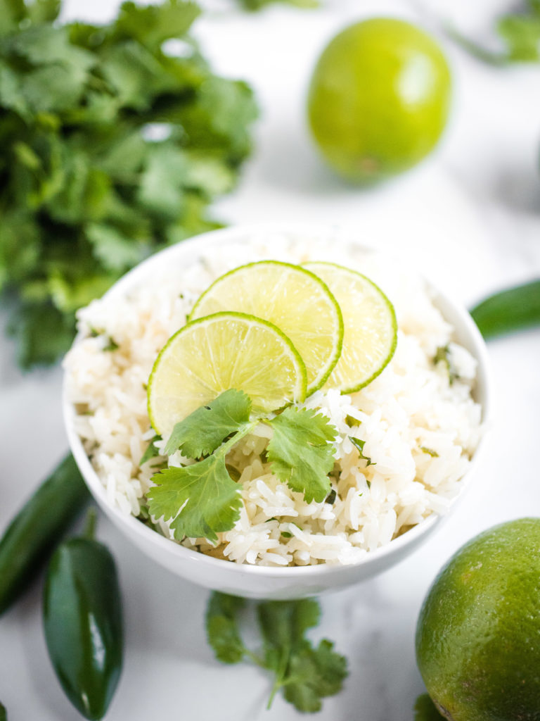 jalapeno lime rice in a white bowl topped with sliced lime and sprig of cilantro