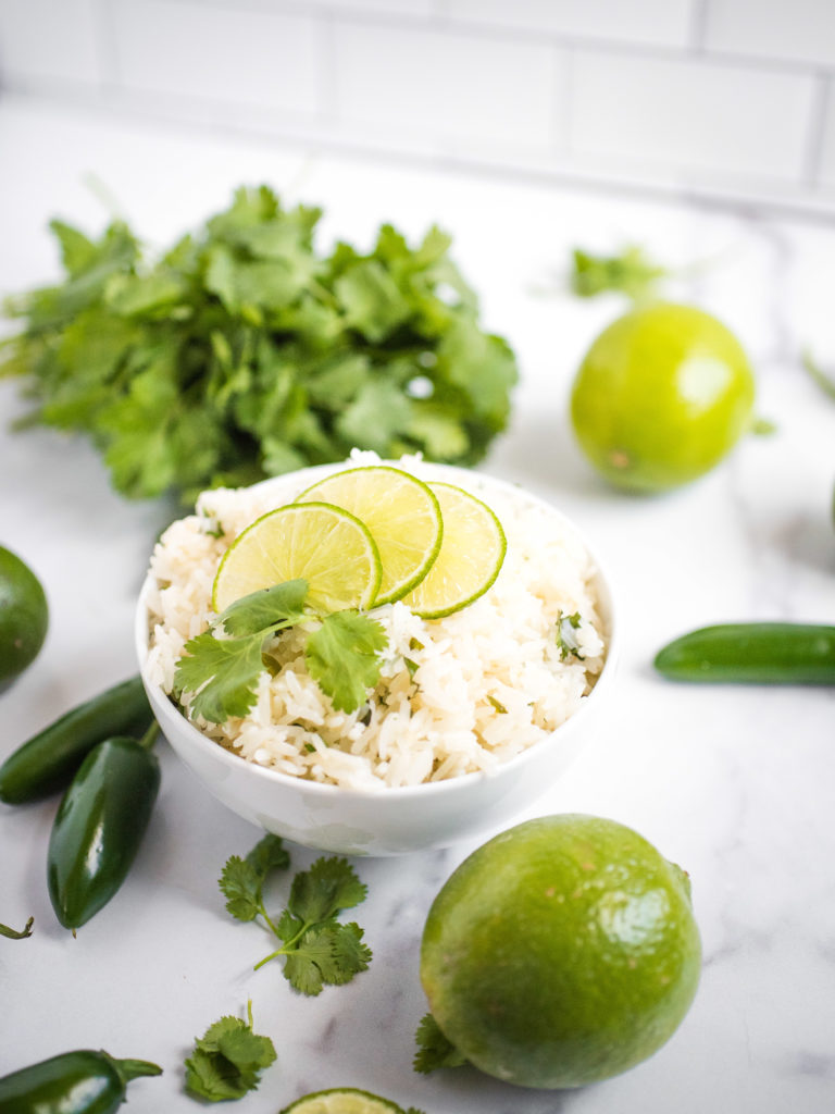 jalapeno lime rice in a white bowl topped with sliced lime and a sprig of cilantro