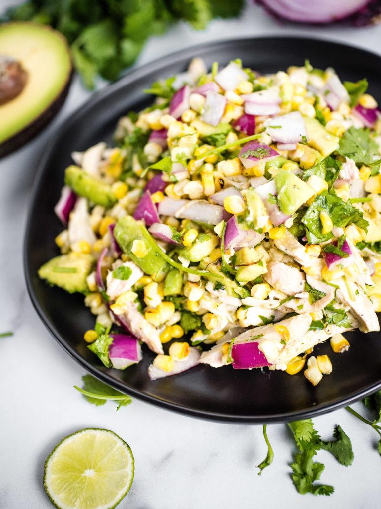 avocado chicken chopped salad on a black plate