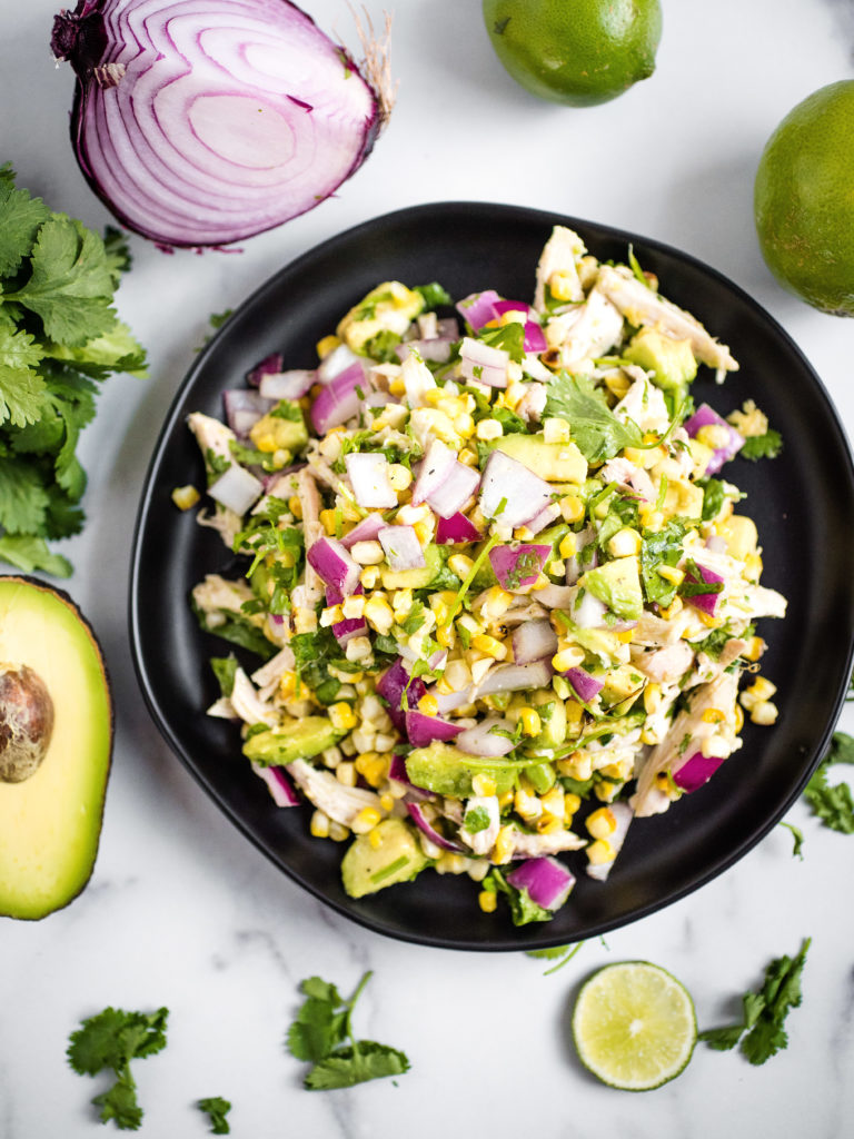 over head shot of avocado chicken chopped salad on a black plate