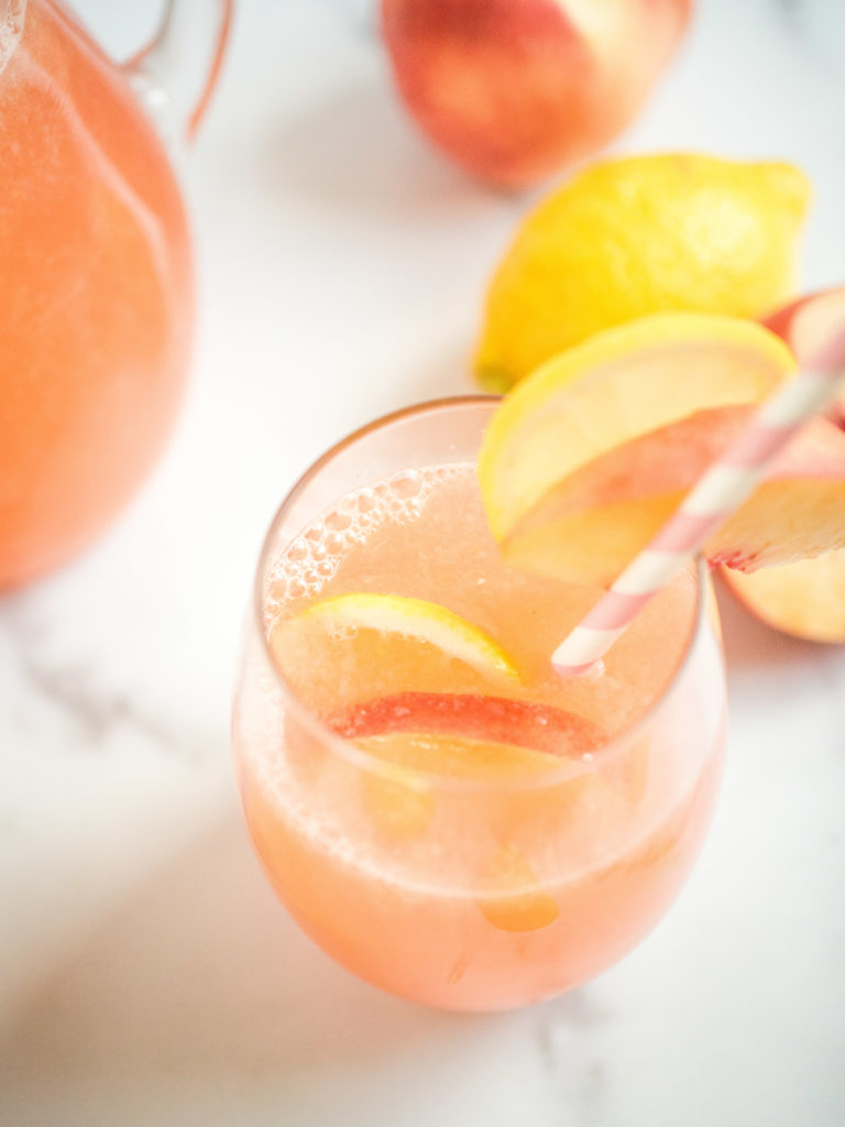 overhead shot of peach lemonade with garnish and lemon and peach in glass