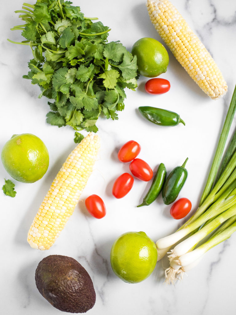 overhead shot of corn, limes, cilantro, tomatoes, jalapeno, avocado, and green onion