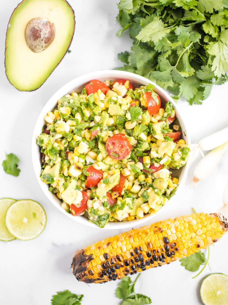 overhead shot of summer corn salad with grilled corn, avocado, cilantro, and lime on the counter around it
