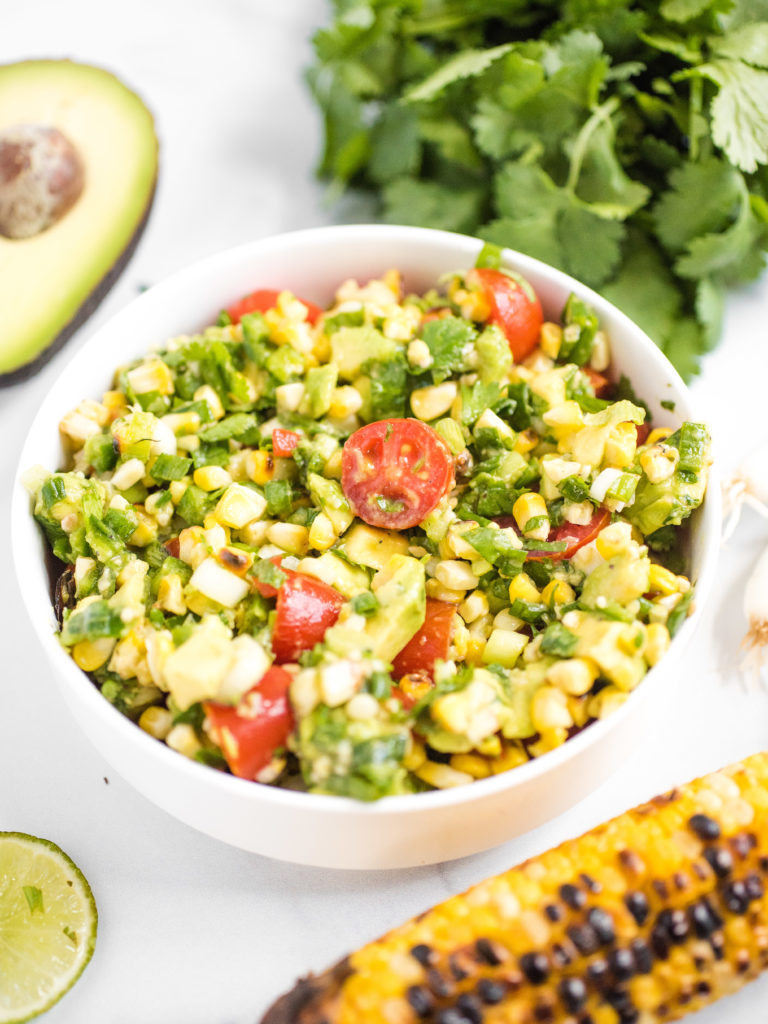bowl of summer corn salad with cilantro and avocado in the background. Grilled corn and lime are in the foreground.