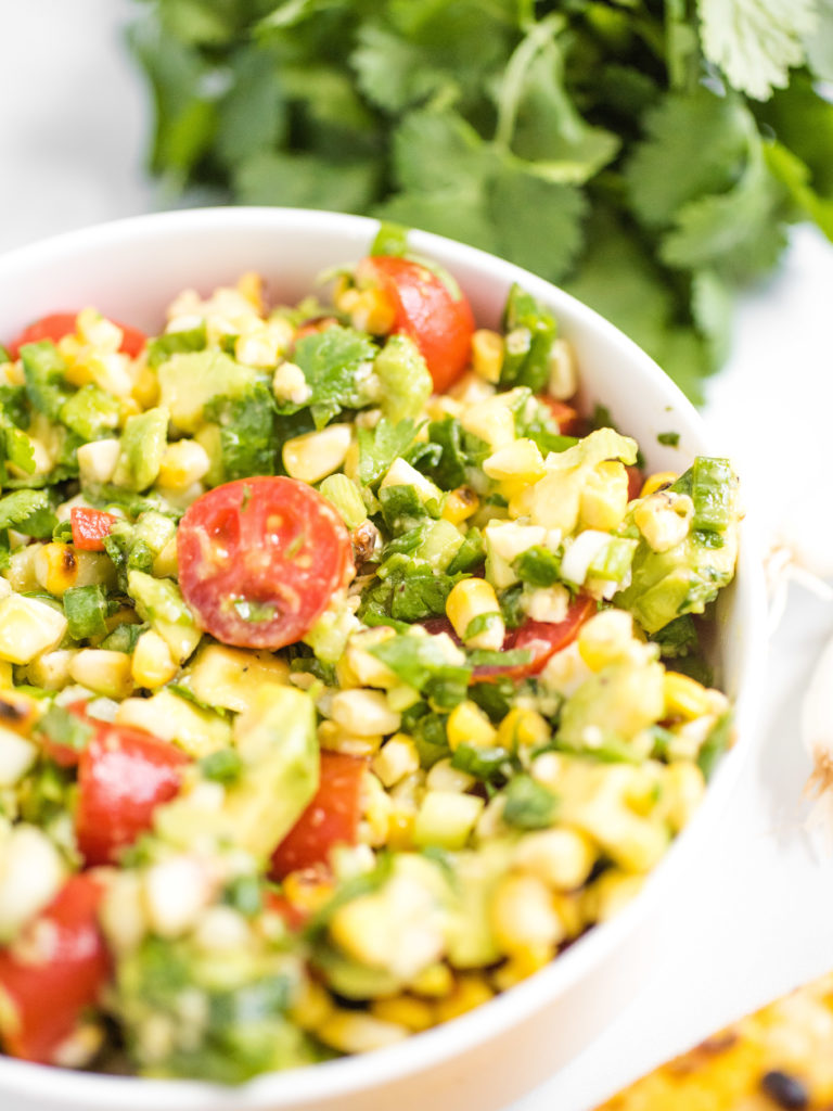 summer corn salad in a white bowl with cilantro in the background