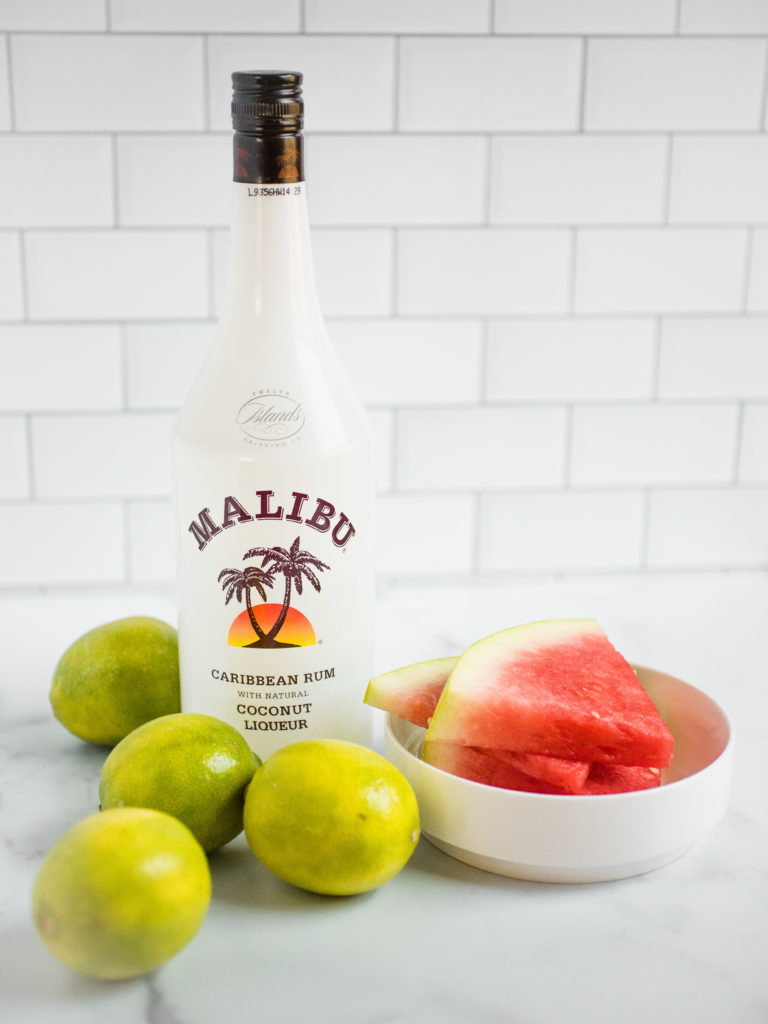 bottle of malibu rum with sliced watermelon in a white bowl surrounded by limes