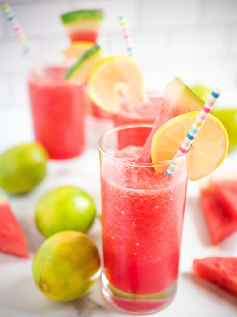 glass of watermelon slush garnished with lime and watermelon with a rainbow paper straw
