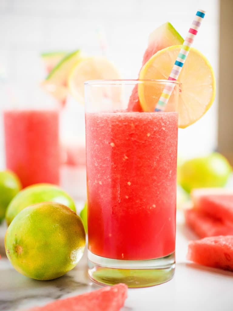 up close shot of watermelon slush garnished with lime and watermelon