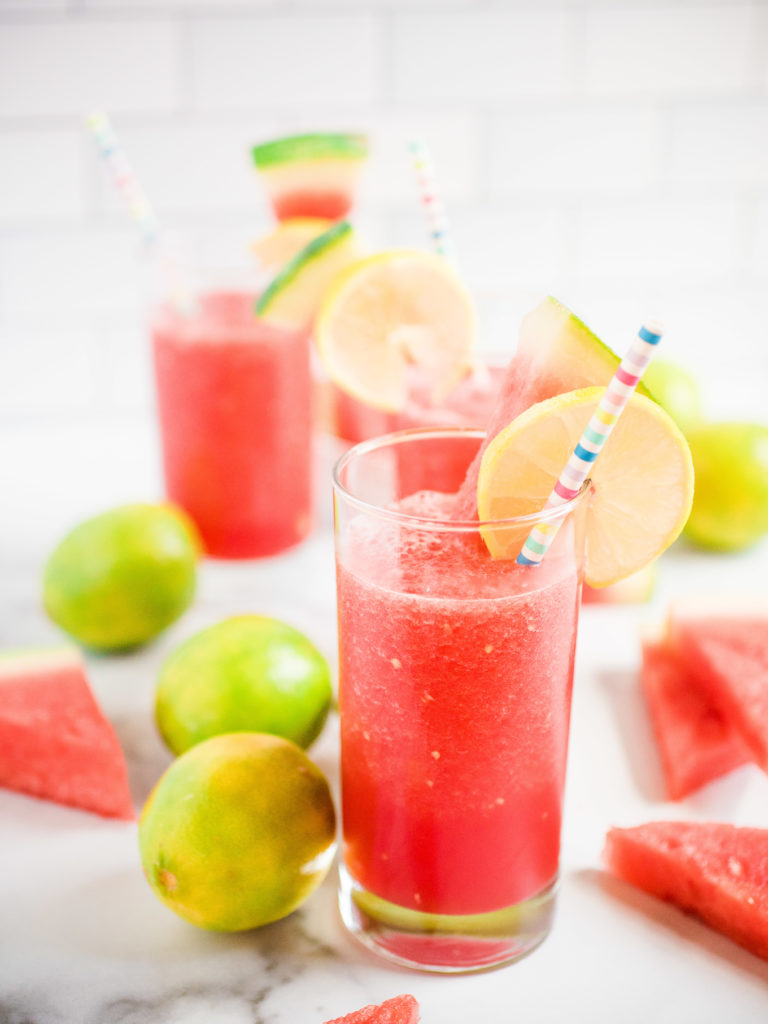 glass of one watermelon slush garnished with lime and watermelon