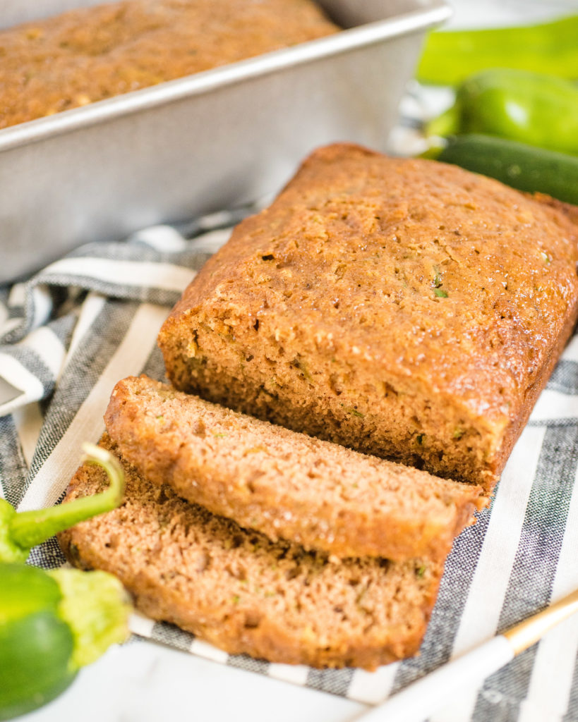 loaf of green chile zucchini bread with two slices cut and laying in front of the rest of the loaf. there is a pan in the background with another loaf.