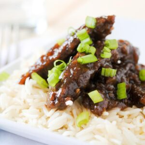 beef teriyaki on white rice on a white plate