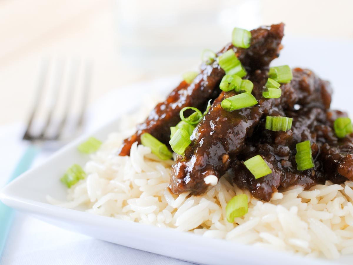 beef teriyaki on white rice topped with green onions on a white plate