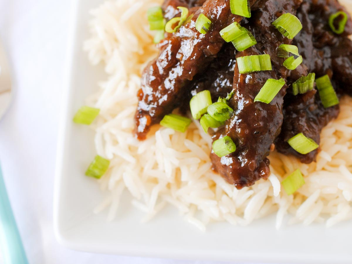 beef teriyaki on a plate of white rice topped with sliced green onions