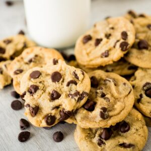 a stack of chocolate chip cookies in front of milk