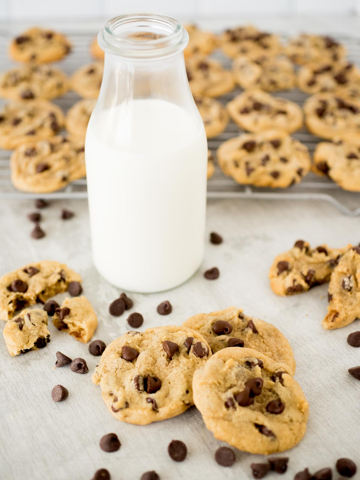 chocolate chip cookies in front of milk and a rack of cooling cookies