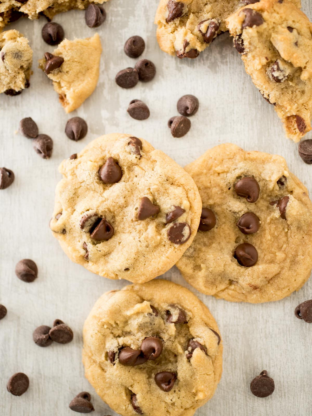 stack of chocolate chip cookies surrounded by chocolate chips