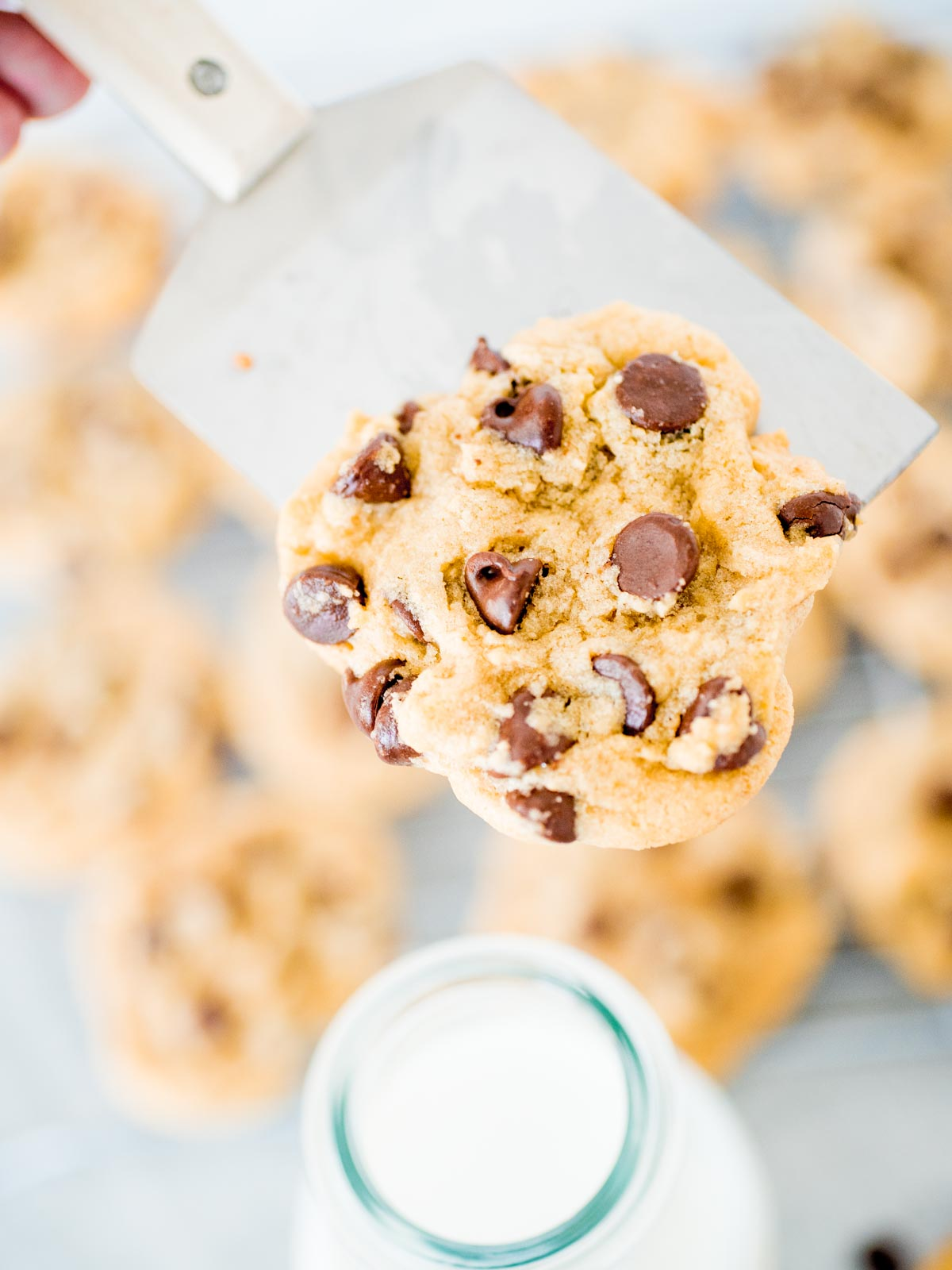 chocolate chip cookie on a spatula over a glass of milk