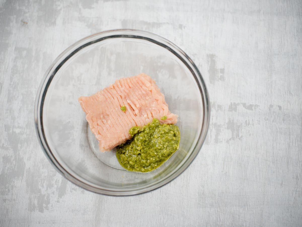 raw chicken and pesto in glass bowl