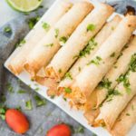 stack of chicken taquitos on a white plate