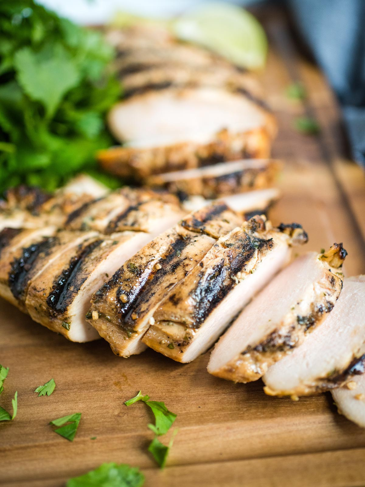 sliced grilled chicken on cutting board