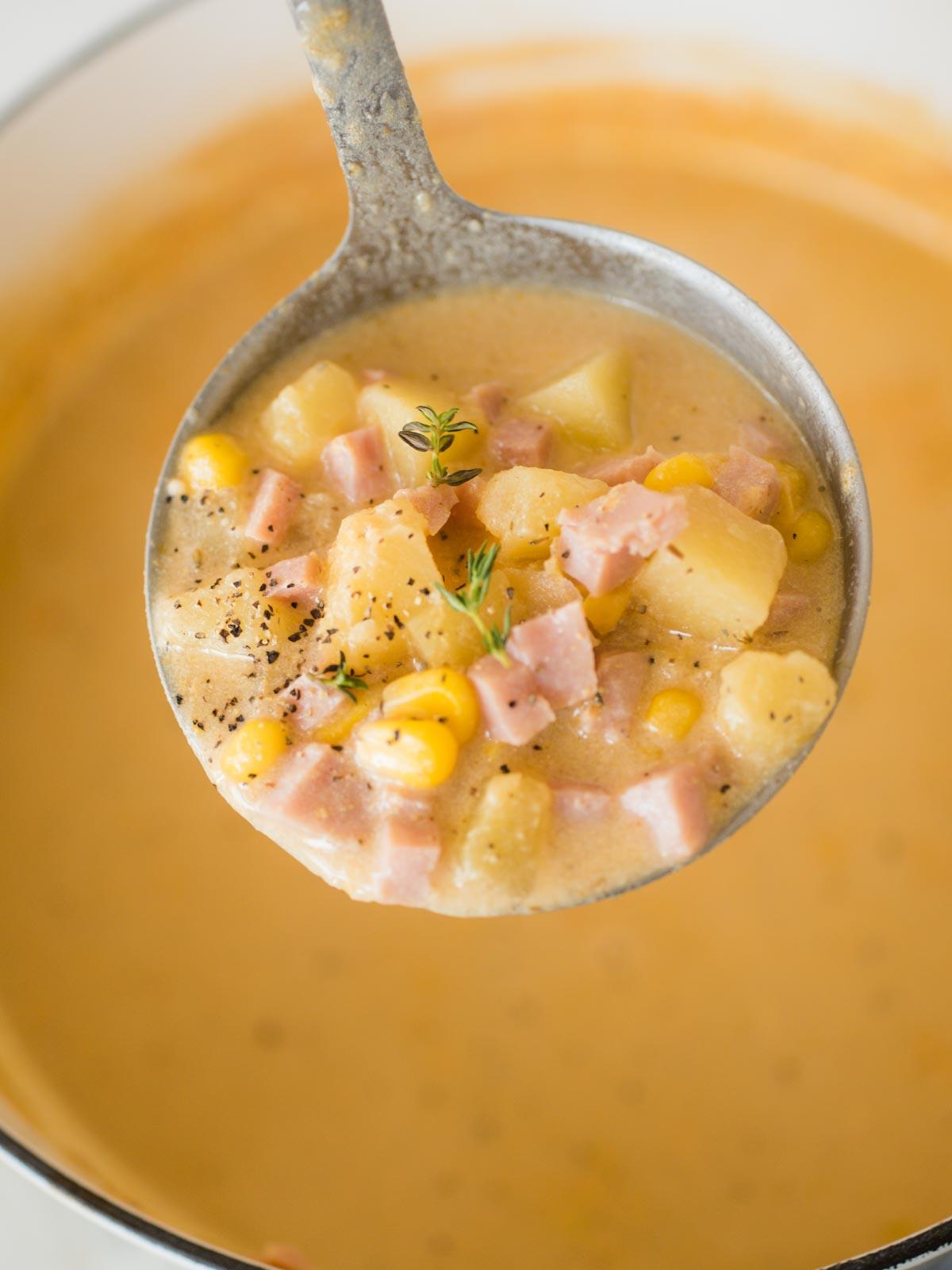 ladel full of creamy ham and potato corn chowder