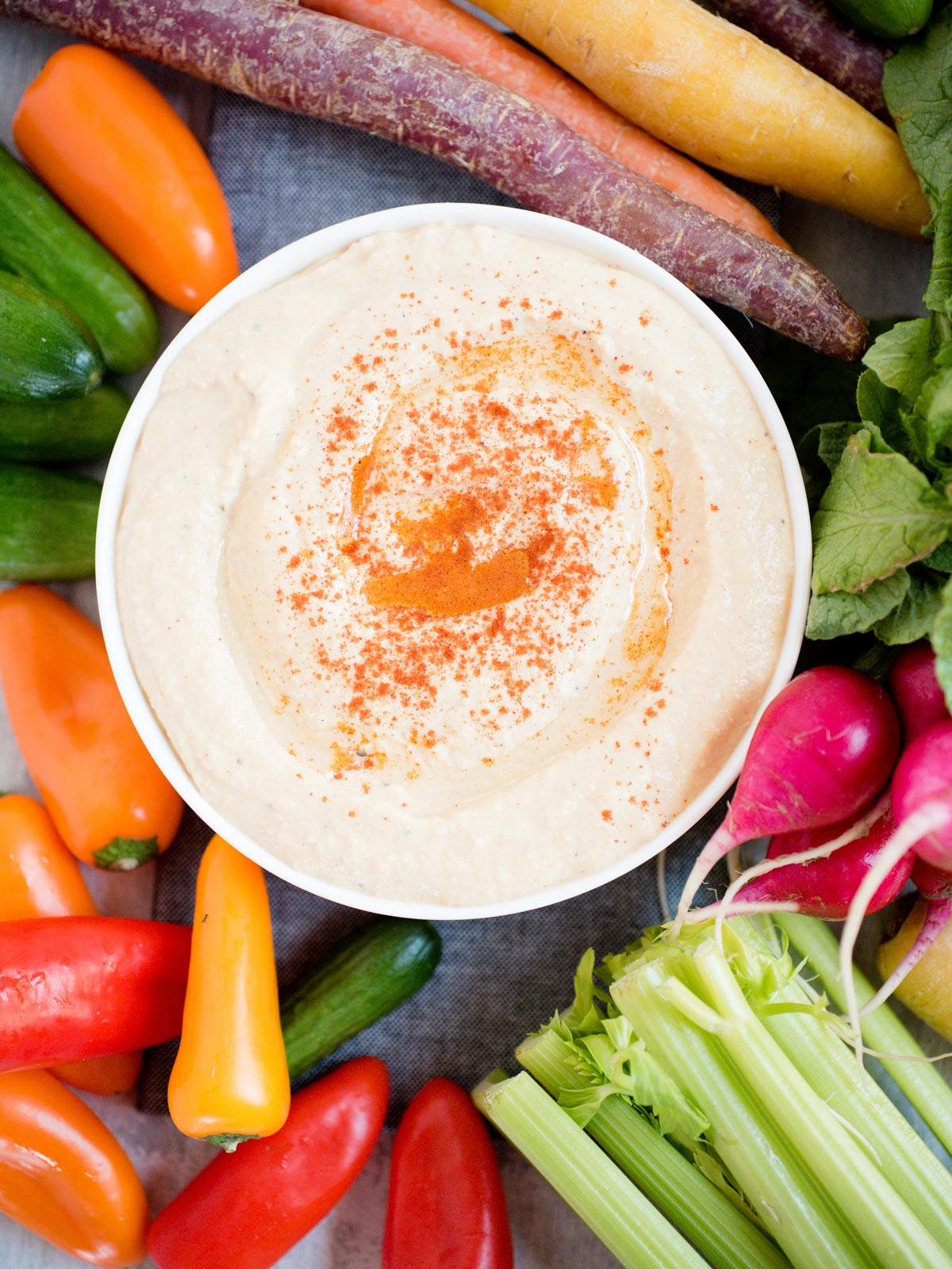 hummus in white bowl sprinkled with paprika