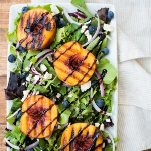 grilled peach salad on a white plate