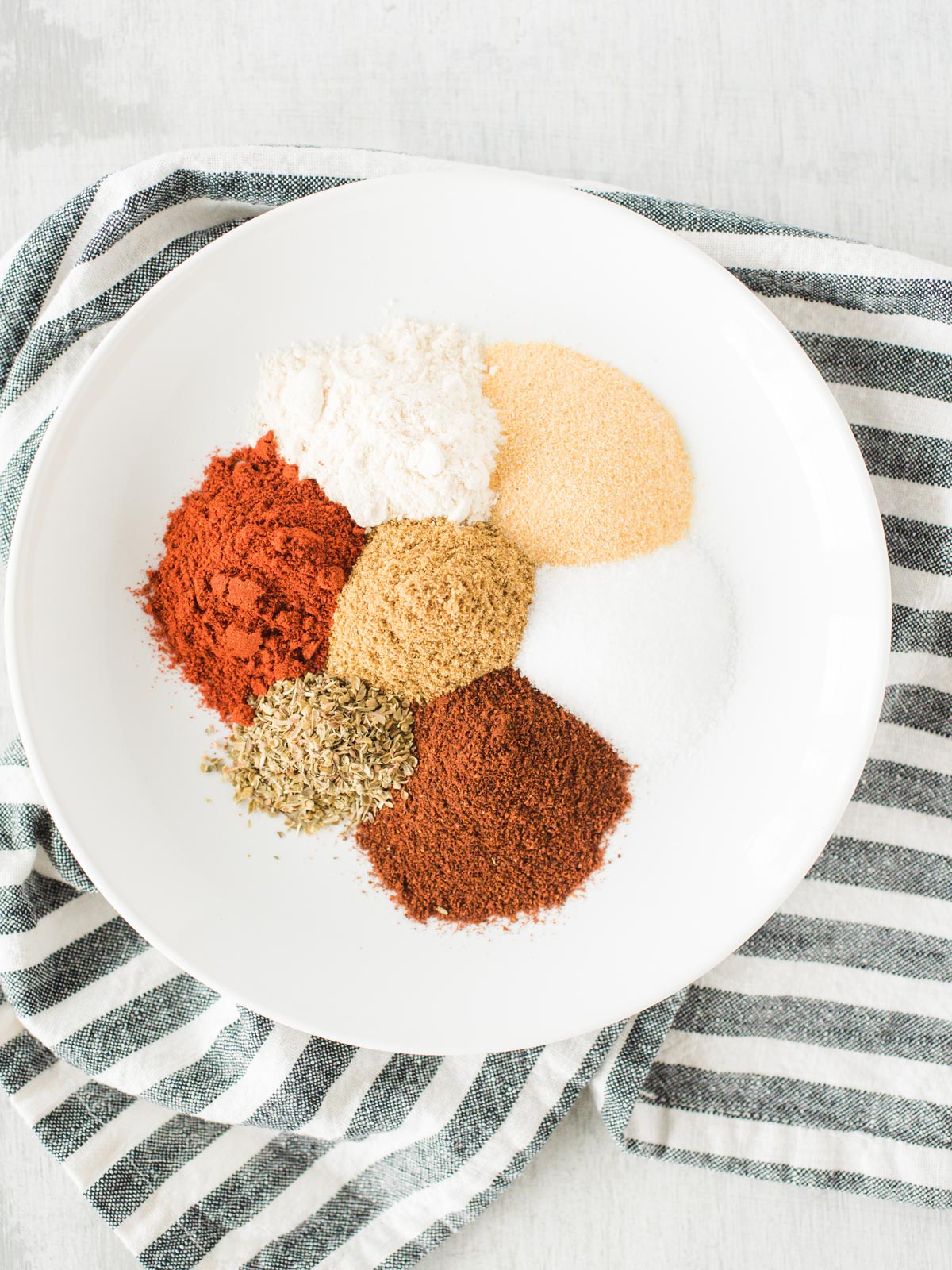 ingredients for taco seasoning on a plate on top of a striped cloth