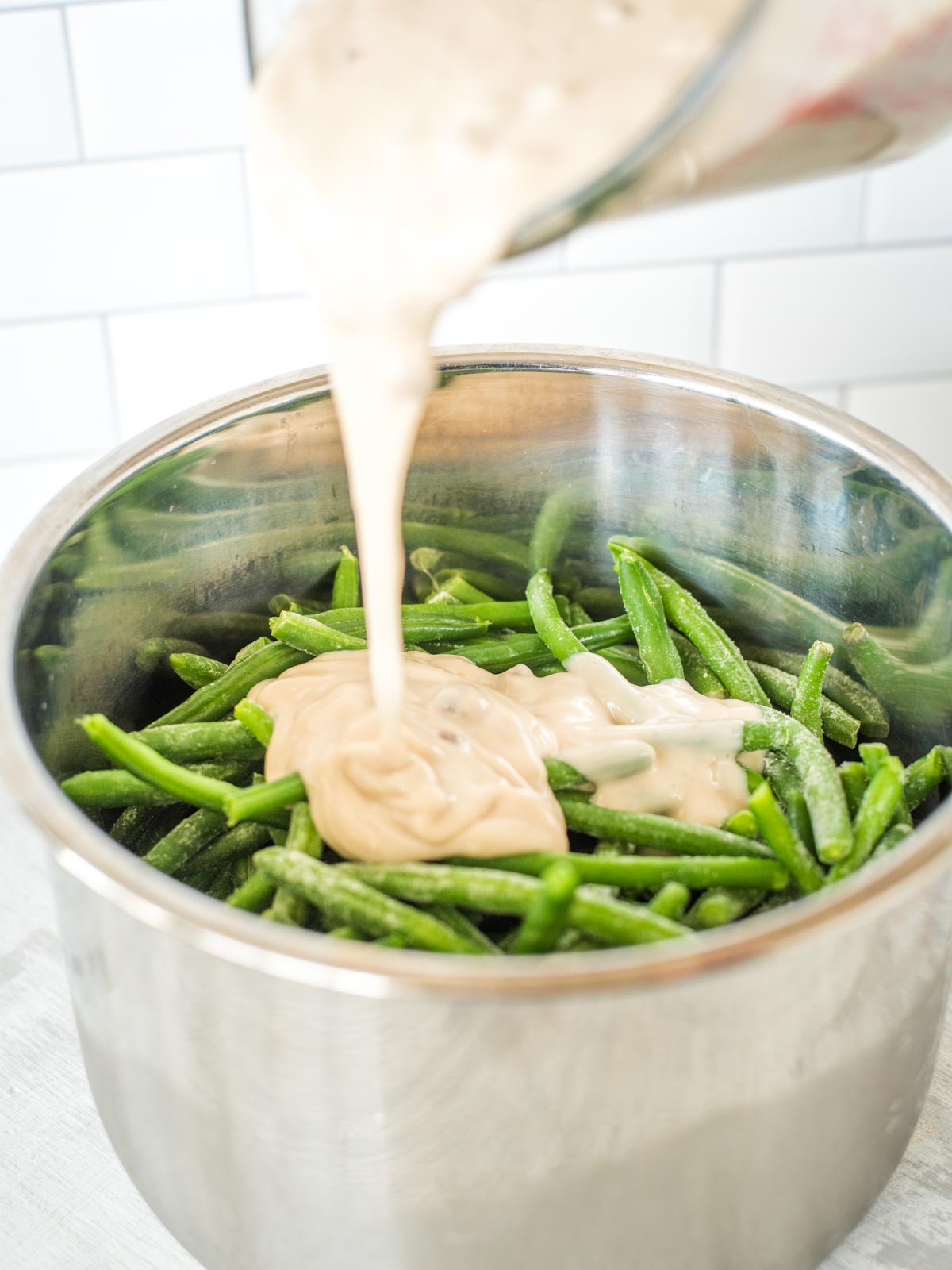 green bean casserole mix being poured into instant pot sleeve