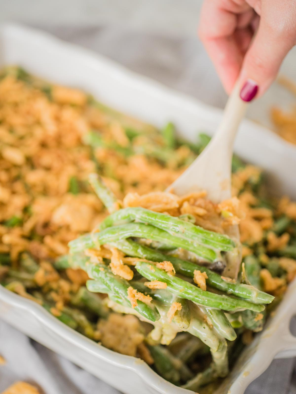 green bean casserole being scooped out of casserole dish
