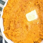 mashed sweet potatoes in a white baking dish topped with butter