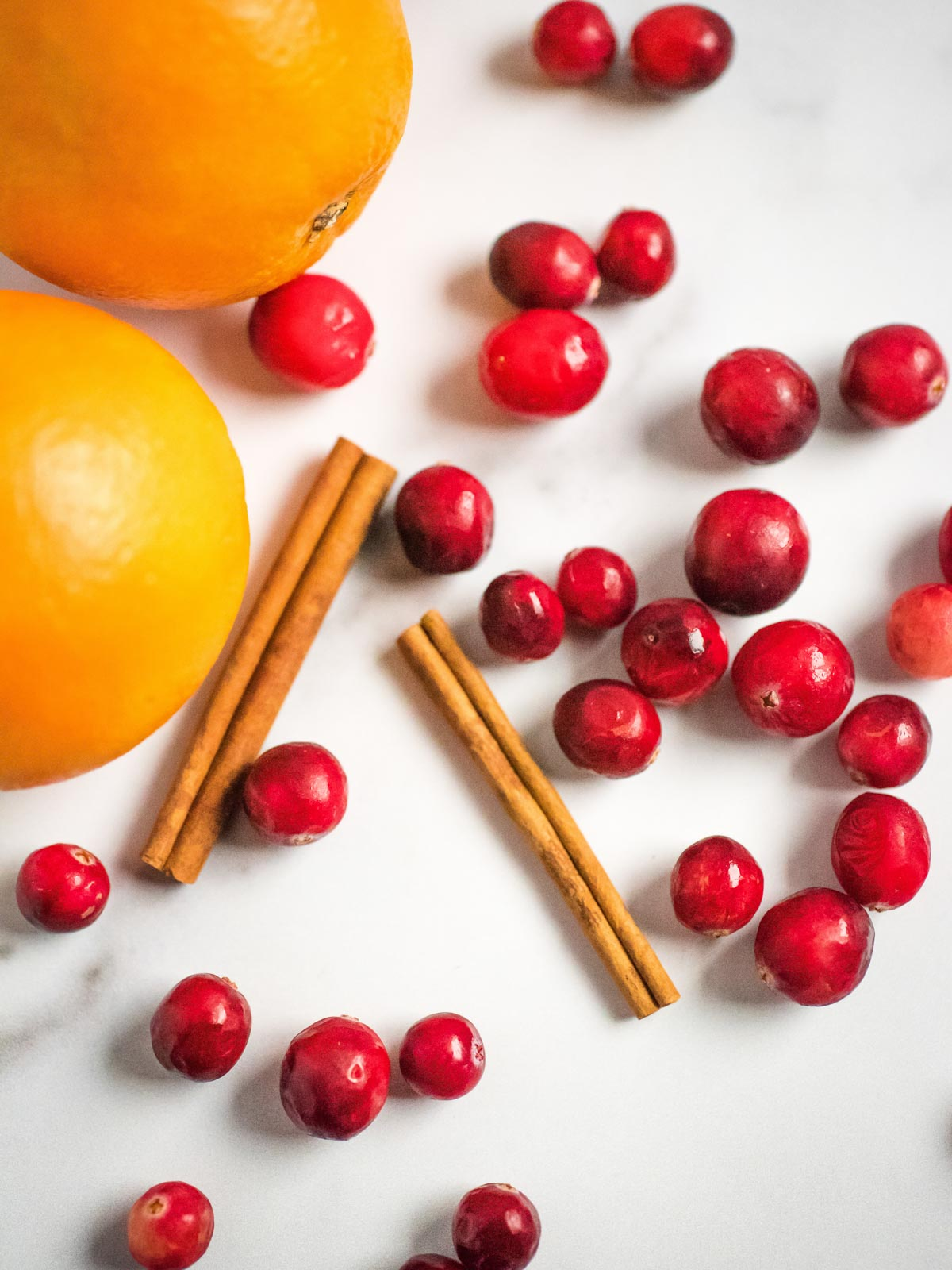 oranges cinnamon sticks and cranberries on the surface