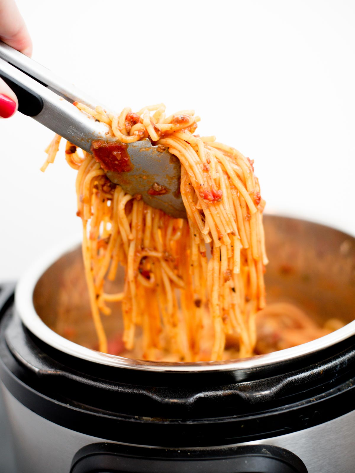 spaghetti being pulled from instant pot with tongs