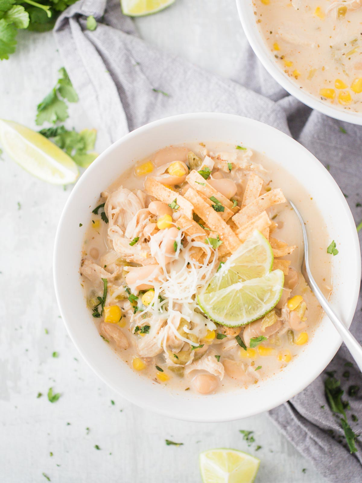 a white bowl full of instant pot white chicken chili with a spoon inside
