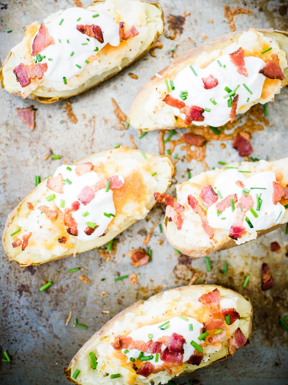 loaded twice baked potatoes on a baking sheet