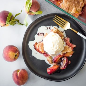 peach cobbler on a black plate topped with ice cream