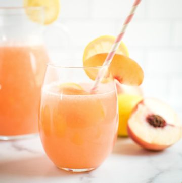 a glass of peach lemonade with a straw