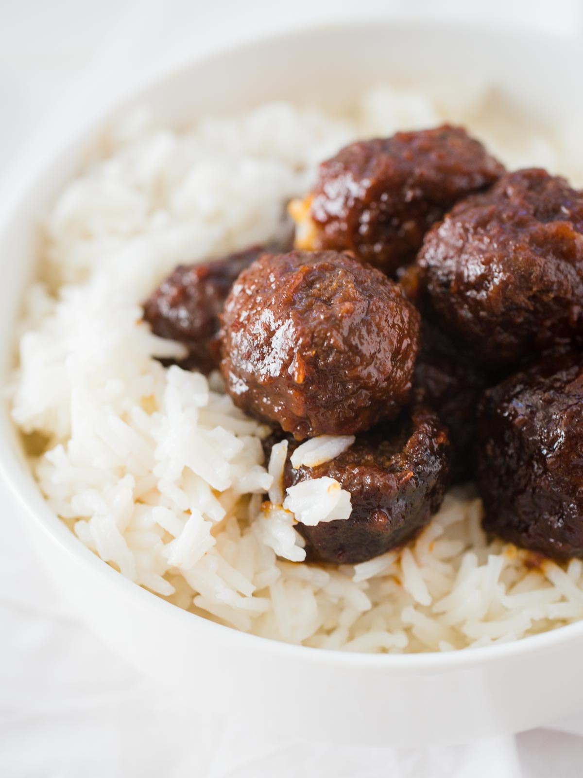 meatballs over rice in a white bowl