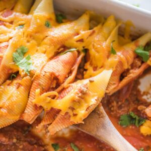 taco stuffed shells being scooped with a wooden spoon