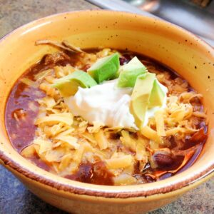 Crockpot Mexican Chili in a yellow bowl topped with cheese, sour cream, and avocado